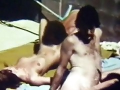 A group of people is playing ball in a swimming pool. Next to it a girl is on her knees, sucking a guys dick. He lays her down on her back to fuck her when another guy approaches to have his dick sucked. Behind them, another girl gets her pussy licked by