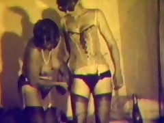 Two women arrive at a house in a Mini, carrying a lot of bags. Next we watch them in the bedroom where both of them have stripped down. One of the girls lies down on the bed and the other one plays with her pussy, poking a dildo inside.