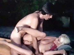 A blonde girl with large pointer sisters is sitting in an outdoor spa. A fellow approaches her, takes his clothes off and then joins her in the water where he begins to lick her curly pussy. She sucks his cock and then the both of them screw next to the pool.
