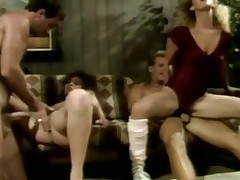 A naked guy is on a couch. This guy is fucking a blonde girl who is sitting on his lap. Next to them another woman is laying on her back. She is getting screwed by a second guy. The other pair receives down on the floor where the first girl is screwed from behind.