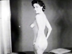 In the first scene of this vintage dark and white episode we see a young woman posing bare in front of the camera. She stands up at first and then kneels down on the floor. In the next scene a bare girl sits in front of a fire reading a book.