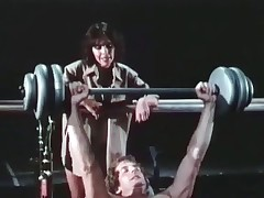 A guy is pushing weights at the gym when his girlfriend comes up to talk to him, telling him to take good care of his body. She then acquires very seductive and they end up sucking and fucking on top of all the equipment.