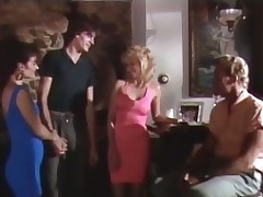 A blonde, busty woman is having a talk with her boyfriend in the middle of a party. The both of them end up in the bedroom where they fuck on the bed, watching themselves in the mirrors on the wall until the guy comes on her ass.