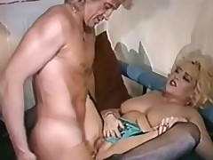 A chubby blonde woman is crouched on her knees on a bed, getting fucked fin her ass by a guy. After a while the stud sits down and she rides his dick, playing with her big milk shakes at the same time.