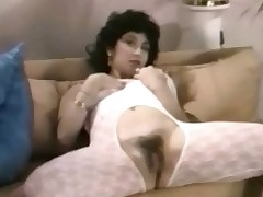 A angel who is dressed in her underwear walks into a room where two guys and another angel are at the table. A little later she is laying down wearing a crotchless catsuit. She lowers the top of it and plays with her massive boobs.