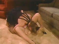 A naked, blond girl is laying on her back on the flor where a girl in lingerie is licking her pussy. Meanwhile, a chap sitting on a couch is watching the two of them. A little later the girls bove into sixty nine position.