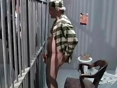 A middle aged woman walks into a prison ward. In one of the cells and elderly man is sitting on a chair with his pants down and slowly jerking off. She bares her tits and watches him in close up until he comes on her face.